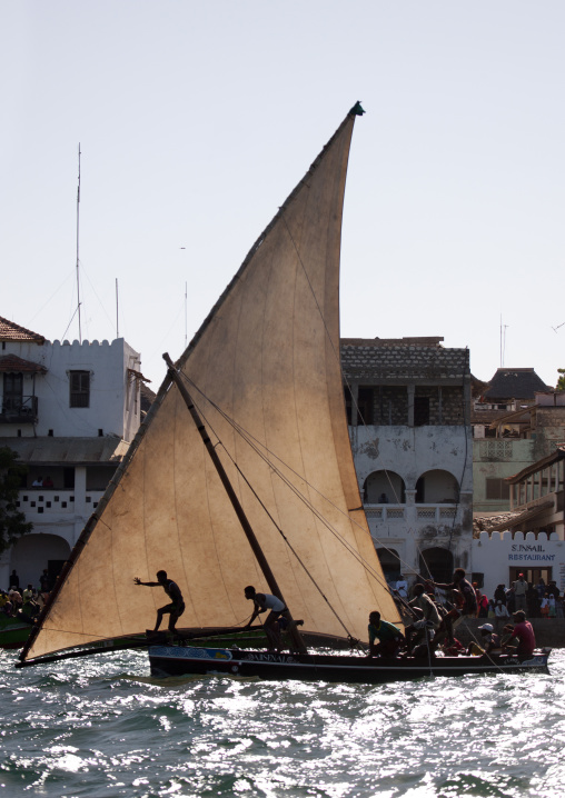 Men steering their dhow near lamu dockside, Lamu, Kenya