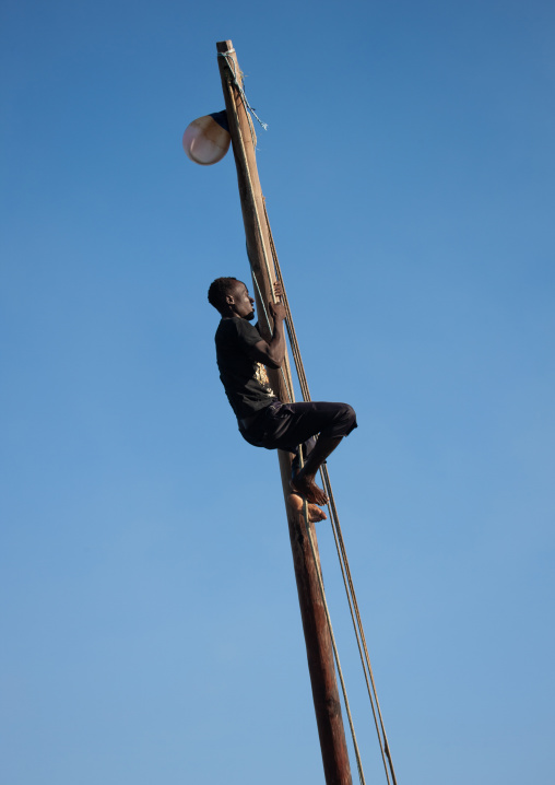 Man climbing a dhow mast, Lamu County, Lamu, Kenya