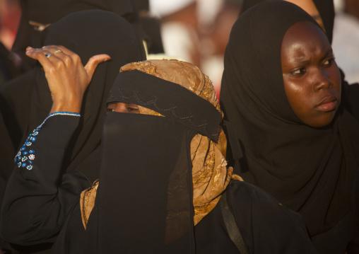 Three young veiled women during maulidi festival, Lamu, Kenya