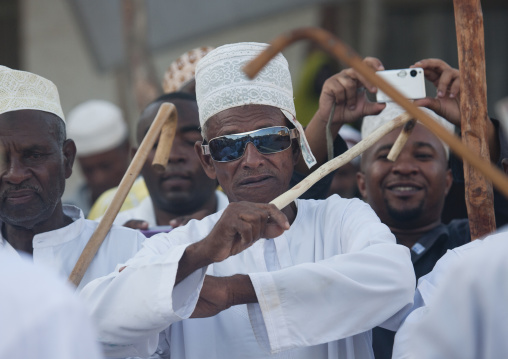 Senior man with sunglasses dancing goma stick dance at maulidi festival, Lamu, Kenya