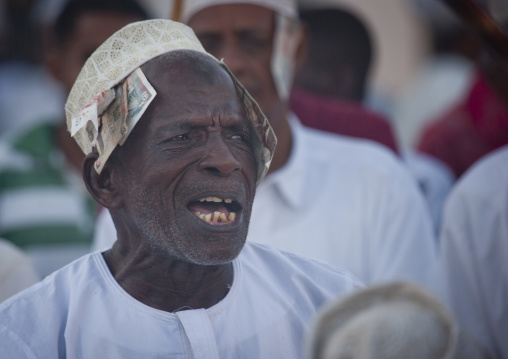 Senior man singing and directing goma stick dance at maulidi festival, Lamu, Kenya