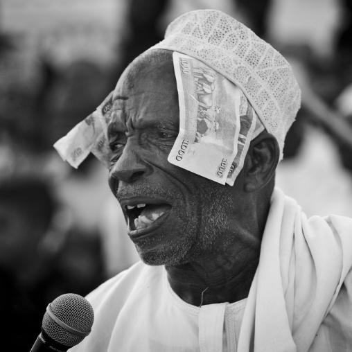 Senior man singing and directing goma stick dance at maulidi festival, Lamu, Kenya