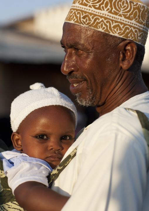 Father carrying small baby girl with coaled eyelids during maulidi, Lamu, Kenya