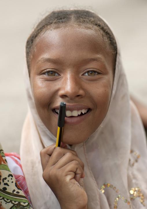 Cute teenage girl smiling with pen, Lamu, Kenya