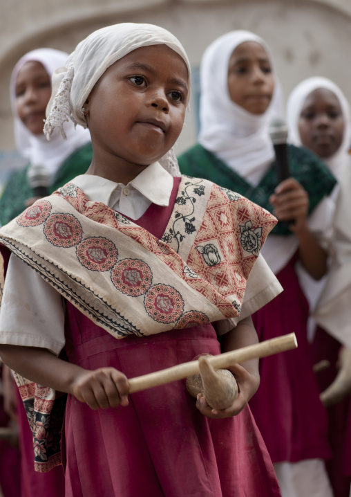 Young girl in traditional suit and holding a stick, Maulidi, Lamu, Kenya