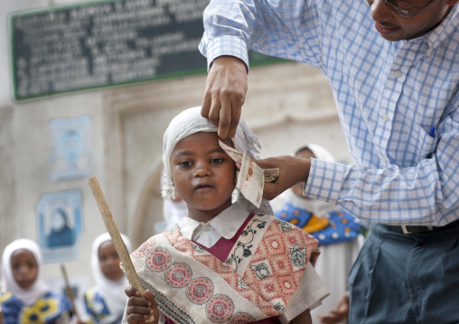 Man putting banknote under young girl's veil in traditional suit and holding a stick, Maulidi, Lamu, Kenya