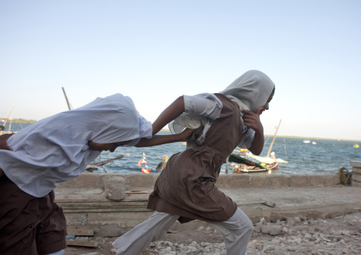 Two schoolgirl teenagers running alongside the dock in lamu, Kenya