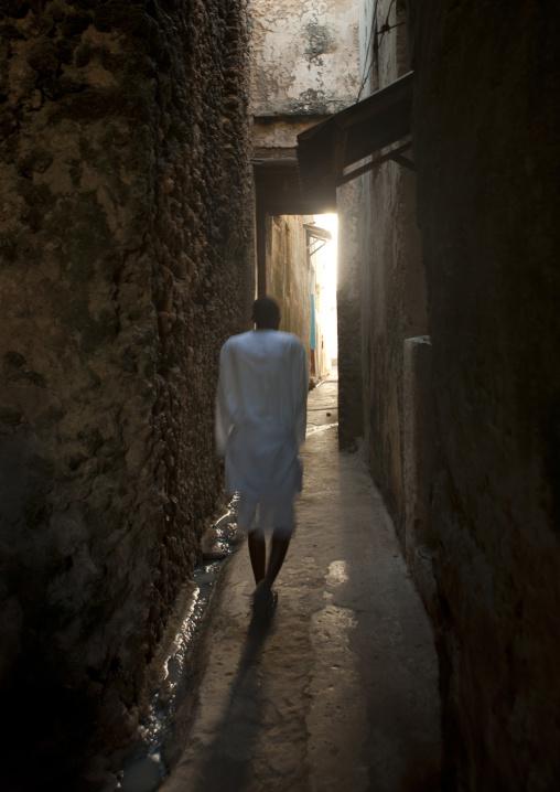 Backside of a man passing by a narrow street of lamu, Kenya