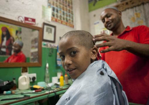 Young boy getting head shaved in barbershop, Lamu, Kenya