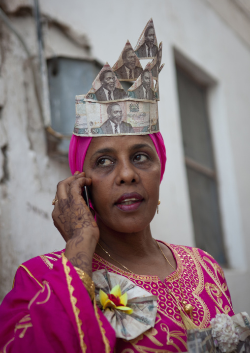 Woman calling with cellphone, Wearing banknotes hat in maulidi festival, Lamu, Kenya