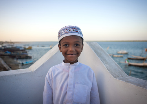 Little boy wearing kofia hat sea background at lamu, Kenya