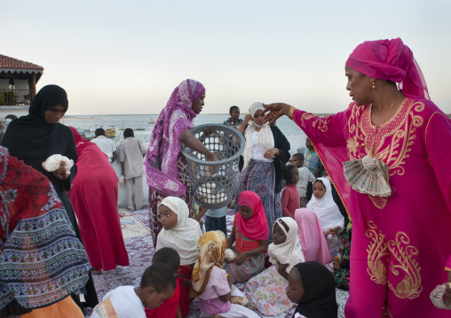 Muslim woman giving food during Maulid festival, Lamu County, Lamu, Kenya