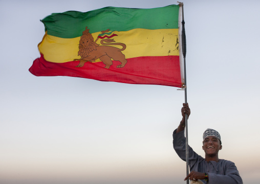 Teenage boy brandishing  ethiopian flag, Rastafari lion, While he smiles at camera, Lamu, Kenya