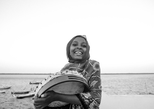 Beauty girl with drum playing on the dockside in lamu, Kenya