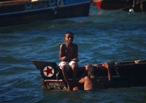 Young boys playing in water prow of dhow, Lamu, Kenya