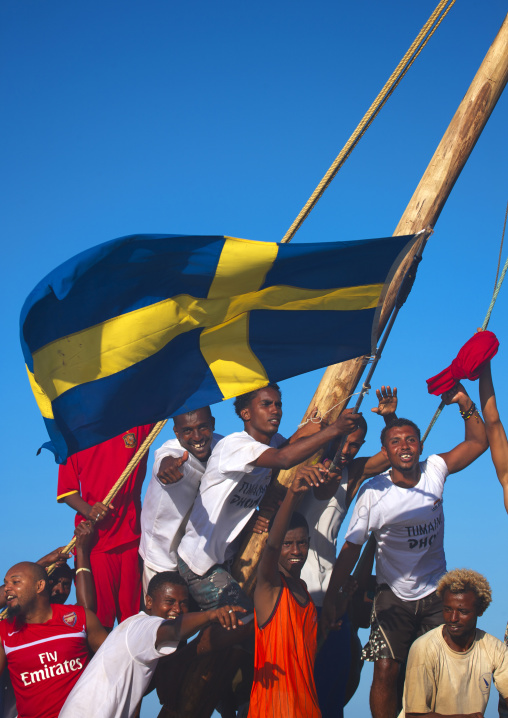 Swedish flagged dhow with crew waving hand and cheering themselves, Maulidi lamu, Kenya