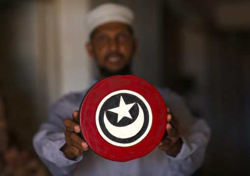Wood carver holding crescent and star sign put on the dhows as lucky sign, Lamu County, Lamu, Kenya