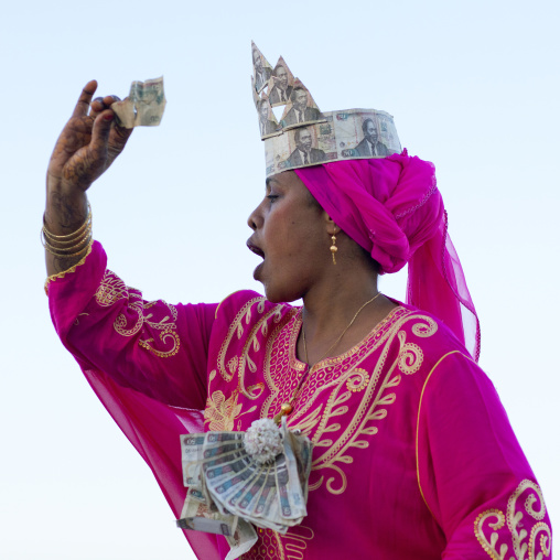 Young woman dressed in pink suit with baknotes hat throwing away, Maulidi, Lamu kenya