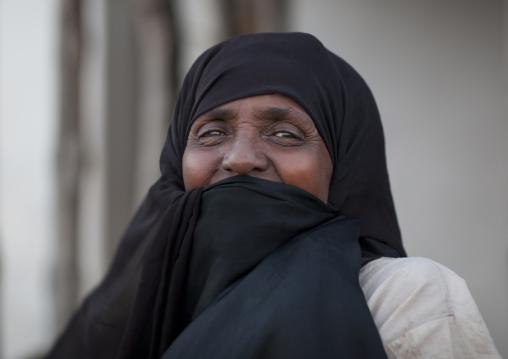 Senior woman with mouth hidden by veil, Lamu, Kenya