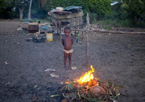 Little girl standing in front of a firecamp, Lamu County, Lamu, Kenya