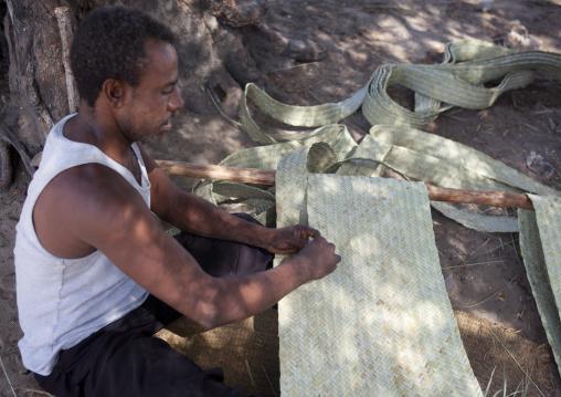 A man weaving a rug sitting on the floor, Lamu, Kenya
