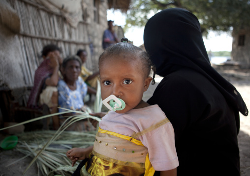 Young woman wearing hijab with light brown skin daughter looking at camera with pacifier in lamu, Kenya