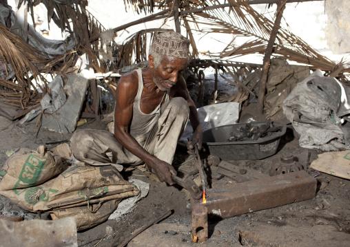 Blacksmith sweating while he forges nails, Lamu County, Lamu, Kenya