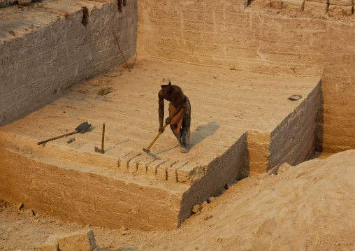 Man cutting off coral stone in the quarry, On manda island, Lamu, Kenya