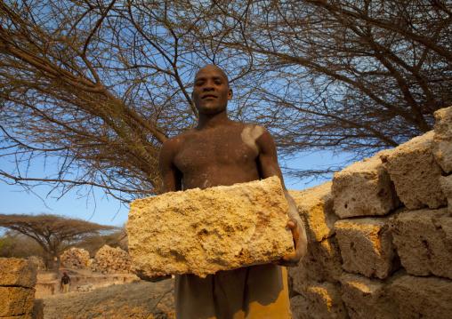 Worker holding yellow stone coral stone quarry, On manda island, Lamu, Kenya