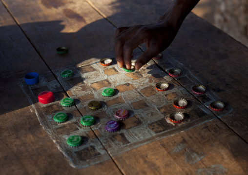 A chessboard with bottle caps pawns and human hand, Lamu, Kenya