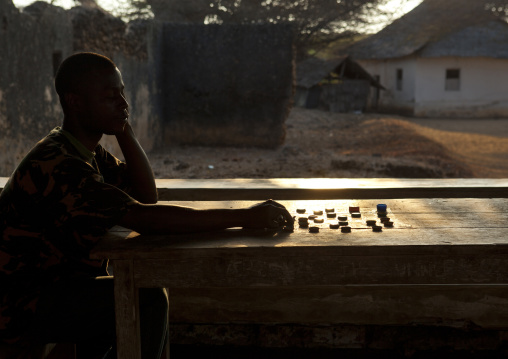 Player contemplative in front of checkerboard, Lamu, Kenya