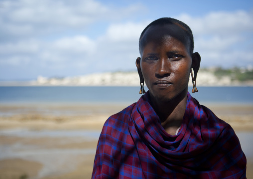 Masai man keeper with shaven head and traditional clothes with sea in the background, Lamu, Kenya