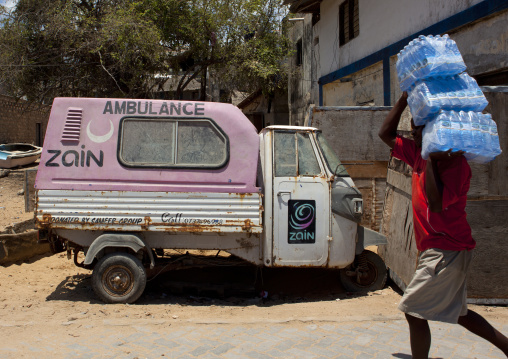 A man carrying drinkable water on his shoulders in front of an ambulance, Lamu County, Lamu, Kenya