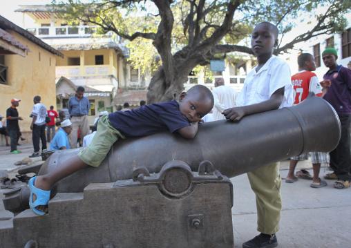 Little boy lazing on a cannon, Lamu County, Lamu, Kenya