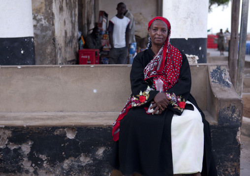 A woman sitting on a concrete bench with traditional dresssing in a street of lamu, Kenya