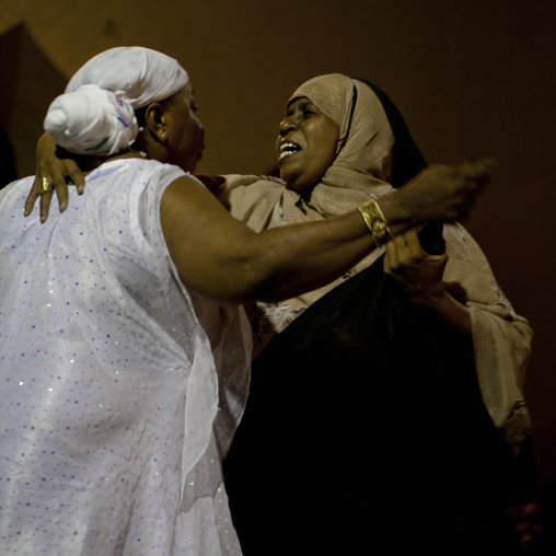 Two mid adult veiled women greeting each other in maulidi festival, Lamu, Kenya