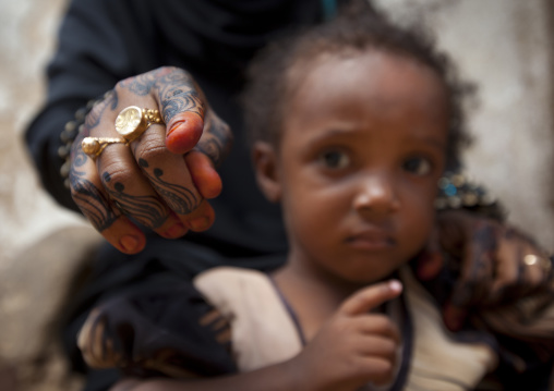 Woman showing camera with henna painted hand, Child worried, Lamu, Kenya