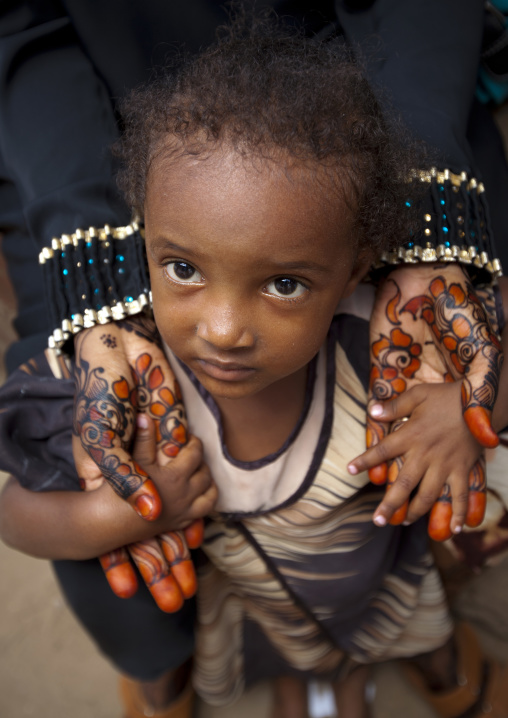 Young girl in the henna painted hands of her mother, Lamu, Kenya