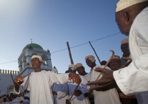 Muslim men singing and dancing with goma sticks during Maulid festival, Lamu County, Lamu, Kenya
