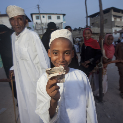Young muslim boy with bank notes he received during Maulid festival, Lamu County, Lamu, Kenya