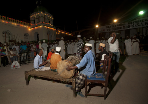 Man playing drums at night on main square, Crowd in background, Lamu, Kenya