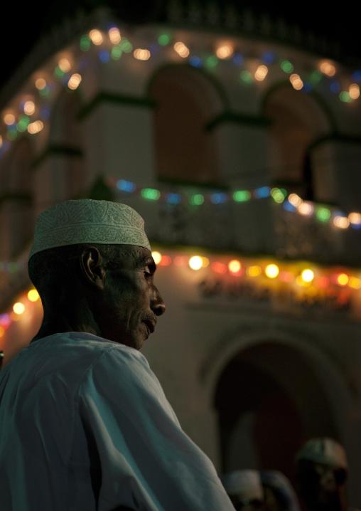 Man standing alone during maulidi, Illumination in background, Lamu, Kenya