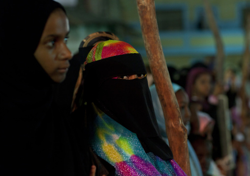 Young veiled women on village square at dusk during maulidi festival, Lamu, Kenya