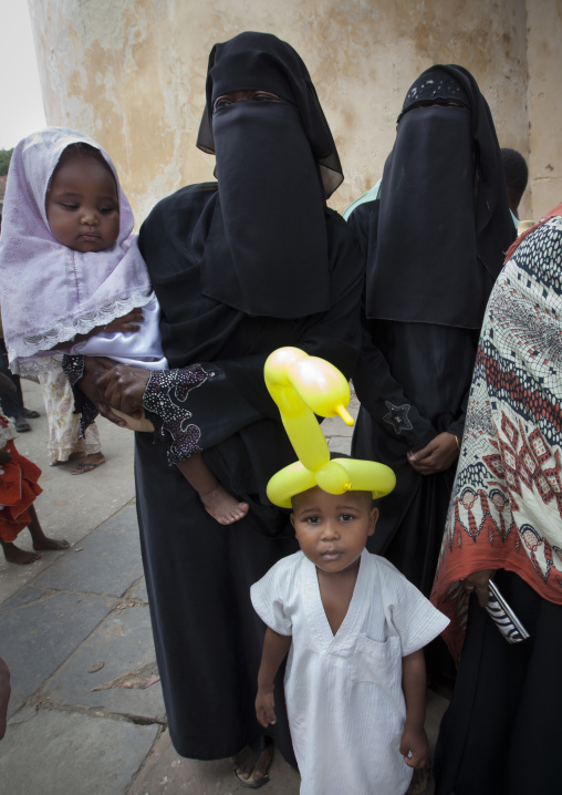 Young woman wearing hijab and child boy with ballon on headin lamu, Kenya