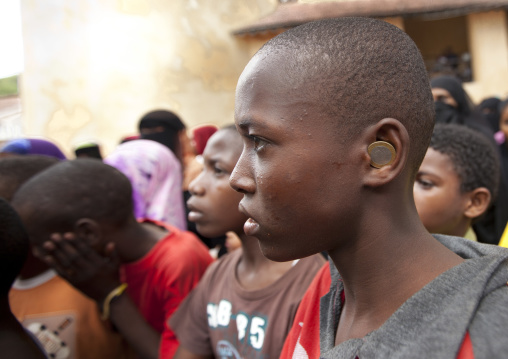 Teenage boy profile with money coin in ear, Lamu County, Lamu, Kenya