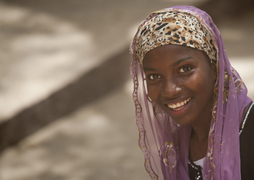 Teenage cute girl in nice posture with veil smiling at camera, Lamu, Kenya
