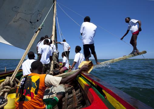Men balancing dhow while sailing during the Maulid festival race, Lamu County, Lamu, Kenya