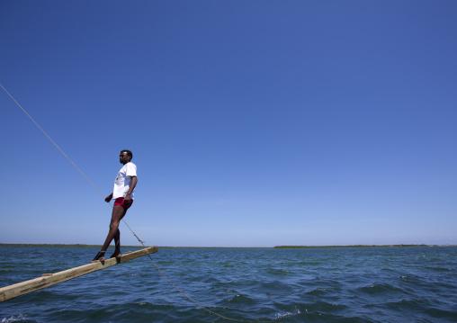 Man balancing dhow while sailing during the Maulid festival race, Lamu County, Lamu, Kenya
