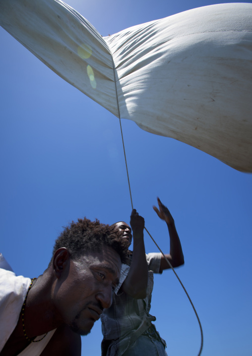 Man raising the sail on a dhow, Lamu County, Lamu, Kenya