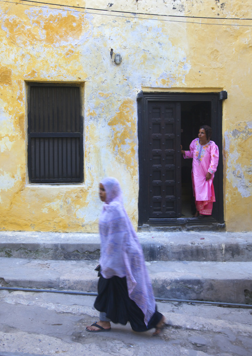 Woman passing in front of an old swahili house in lamu town - kenya